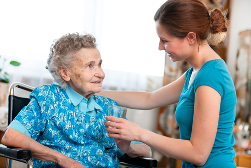 smiling nurse with elderly woman in a wheelchair